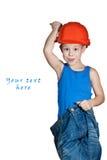 Niño pequeño con el sombrero duro y en pantalones vaqueros demasiado grandes Fotos de archivo
