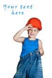 Niño pequeño con el sombrero duro y en pantalones vaqueros demasiado grandes Imagen de archivo libre de regalías