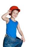 Niño pequeño con el sombrero duro y en pantalones vaqueros demasiado grandes Fotos de archivo libres de regalías