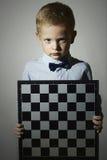 Niño pequeño con el tablero de ajedrez Juego inteligente emoción serio Fotos de archivo libres de regalías