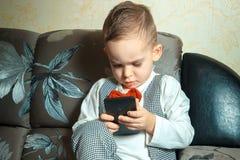 Niño pequeño con el teléfono móvil Imágenes de archivo libres de regalías