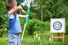 Niño pequeño con el tiroteo grande del arco en objetivo del deporte Foto de archivo