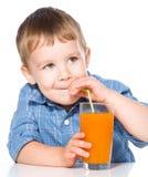 Niño pequeño con el vidrio de jugo de zanahoria Foto de archivo libre de regalías