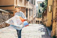 Niño pequeño con estancia del mapa de la ciudad en la calle italiana vieja imagen de archivo libre de regalías