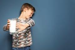 Niño pequeño con la alergia de la lechería que sostiene el vidrio de leche imagen de archivo libre de regalías