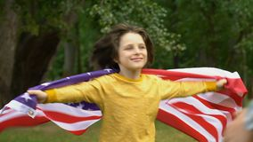 Niño pequeño con la bandera americana que abraza al papá militar, valores familiares, patriotismo almacen de metraje de vídeo