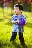 Niño pequeño con la bola púrpura foto de archivo