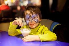 Niño pequeño con la cara pintada como mariposa, comiendo el helado Foto de archivo libre de regalías