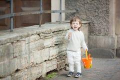 Niño pequeño con la colocación gritadora larga del pelo rubio en la calle En su mano él está sosteniendo un cubo anaranjado para  fotos de archivo