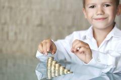 Niño pequeño con la columna de la moneda Imagenes de archivo
