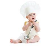 Niño pequeño con la cuchara del metal y el sombrero del cocinero aislados Fotos de archivo libres de regalías
