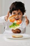 Niño pequeño con la hamburguesa Imagen de archivo libre de regalías