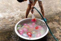 Niño pequeño con la manguera del agua que llena los globos de agua coloridos en cubo fotos de archivo