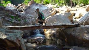 Niño pequeño con la mochila que camina en el puente peligroso sobre el río rápido mientras que verano que camina en montaña Escal metrajes