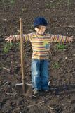 Niño pequeño con la pala grande en el campo Fotografía de archivo