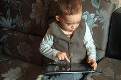 Niño pequeño con la tableta Imagen de archivo