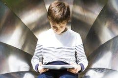 Niño pequeño con la tableta al aire libre Fondo de la textura del metal Escuela, educación, aprendiendo, tecnología, concepto del Foto de archivo
