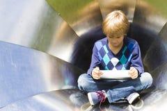 Niño pequeño con la tableta al aire libre Niño que mira abajo a la pantalla Fondo de la textura del metal Escuela, educación Fotografía de archivo libre de regalías