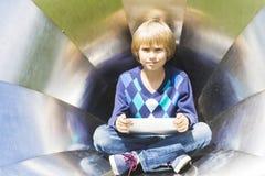 Niño pequeño con la tableta al aire libre Niño que mira derecho Fondo de la textura del metal Escuela, educación, aprendiendo Foto de archivo