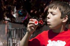 Niño pequeño con las burbujas de jabón en parque del verano Imagen de archivo libre de regalías