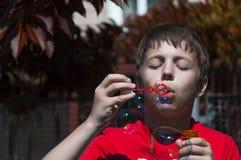 Niño pequeño con las burbujas de jabón en parque del verano Fotografía de archivo