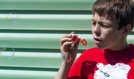 Niño pequeño con las burbujas de jabón en un fondo verde Imagen de archivo