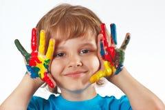 Niño pequeño con las manos pintadas en el fondo blanco Imágenes de archivo libres de regalías