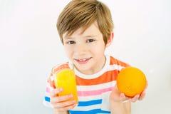 Niño pequeño con las naranjas y el jugo Objeto en blanco Imagen de archivo libre de regalías