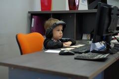 Niño pequeño con los auriculares que se sientan en el ordenador en oficina Imágenes de archivo libres de regalías