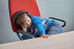 Niño pequeño con los auriculares que se sientan en el ordenador en oficina Imagenes de archivo