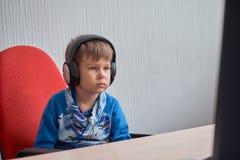Niño pequeño con los auriculares que se sientan en el ordenador en oficina Fotos de archivo libres de regalías