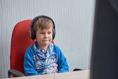 Niño pequeño con los auriculares que se sientan en el ordenador en oficina Foto de archivo