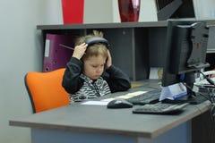 Niño pequeño con los auriculares que se sientan en el ordenador en oficina Fotos de archivo