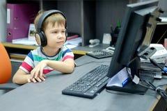 Niño pequeño con los auriculares que se sientan en el ordenador en oficina Fotografía de archivo libre de regalías