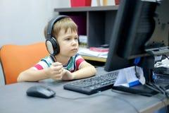 Niño pequeño con los auriculares que se sientan en el ordenador en oficina Foto de archivo libre de regalías