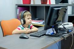 Niño pequeño con los auriculares que se sientan en el ordenador en oficina Fotografía de archivo