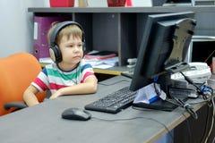 Niño pequeño con los auriculares que se sientan en el ordenador en oficina Imagen de archivo libre de regalías