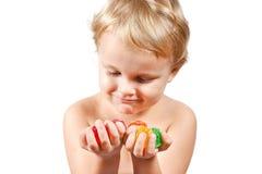Niño pequeño con los caramelos coloreados de la jalea Imagen de archivo libre de regalías