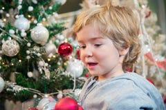 Niño pequeño con los ornamentos de la Navidad Imágenes de archivo libres de regalías