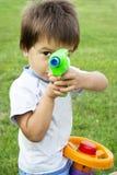 Niño pequeño con un arma del juguete fotos de archivo