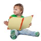 Niño pequeño con un libro que se sienta en el piso Fotografía de archivo libre de regalías