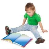 Niño pequeño con un libro que se sienta en el piso Foto de archivo libre de regalías