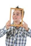 Niño pequeño con un marco en sus manos Fotografía de archivo