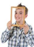Niño pequeño con un marco en sus manos Fotografía de archivo libre de regalías