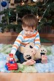 Niño pequeño con un oso de peluche y una máquina en el árbol de navidad Imágenes de archivo libres de regalías