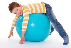 Niño pequeño con una bola grande Fotos de archivo