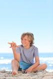 Niño pequeño con una estrella de mar Foto de archivo libre de regalías