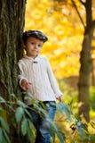 Niño pequeño con una hoja grande en el parque Foto de archivo libre de regalías