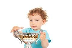 Niño pequeño con una taza del oro Imagenes de archivo