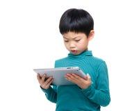 Niño pequeño de Asia que usa la tableta Fotos de archivo